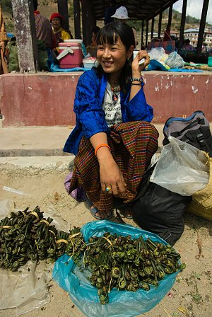 Vendor with fern shoots at the market