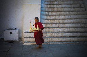 Small monk carrying the offering in Paro dzong